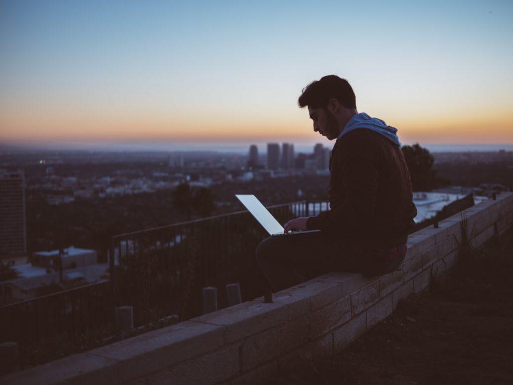 外でパソコンを触る人